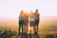 友と肩を組む